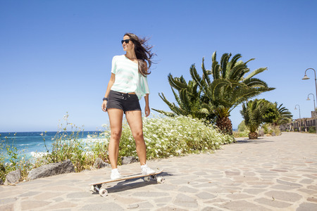 longboard: beautiful young skater woman with a longboard near the sea Stock Photo