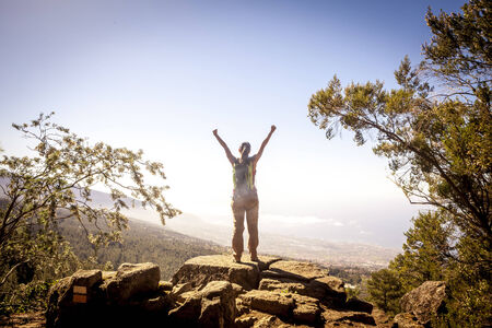 young woman on top of the moutain with the arms raised enjoying freedom. photo