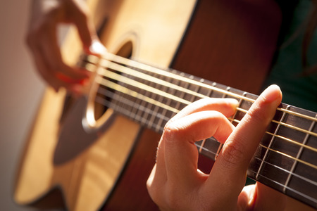 womans hands playing acoustic guitar, close up photo