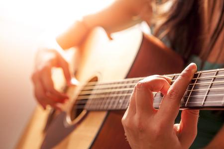 bàn tay của người phụ nữ chơi đàn guitar acoustic, đóng lên