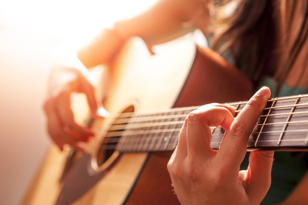 woman's hands playing acoustic guitar, close up Stock Photo