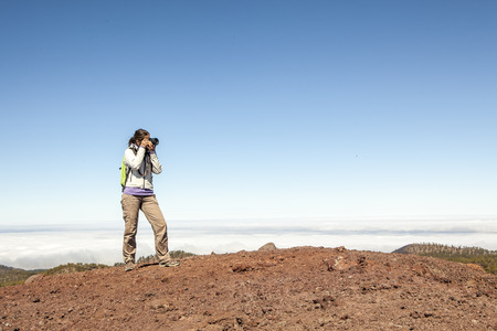 Woman nature Photographer taking pictures outdoors during hiking trip photo