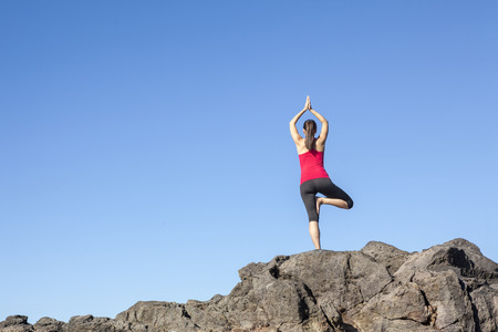 Young woman practicing tree yoga pose outdoor against blue sky photo