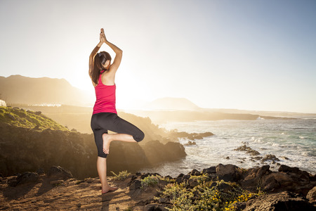 Young woman practicing tree yoga pose near the ocean during sunset Stock Photo