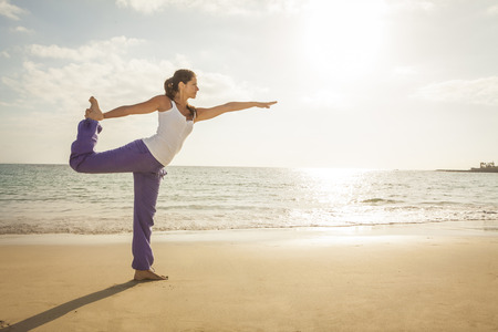 Young woman practicing dancer yoga pose on the beach during sunset photo