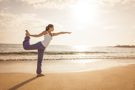 Young woman practicing dancer yoga pose on the beach during sunset