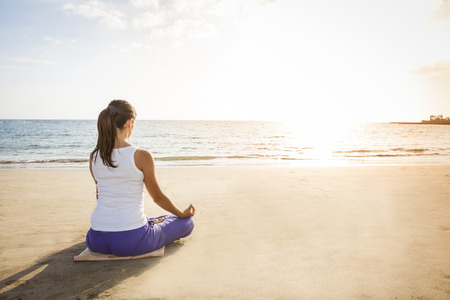 young woman practicing yoga meditation on the beach at sunset photo