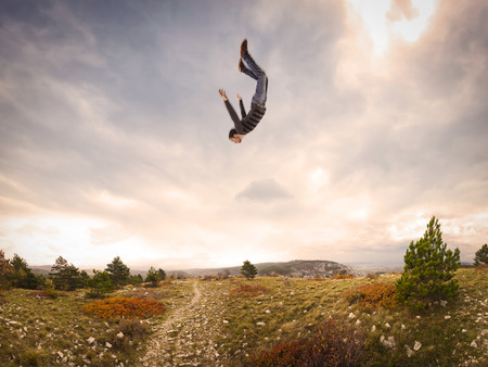 down: man falling down from the sky in autumnal landscape