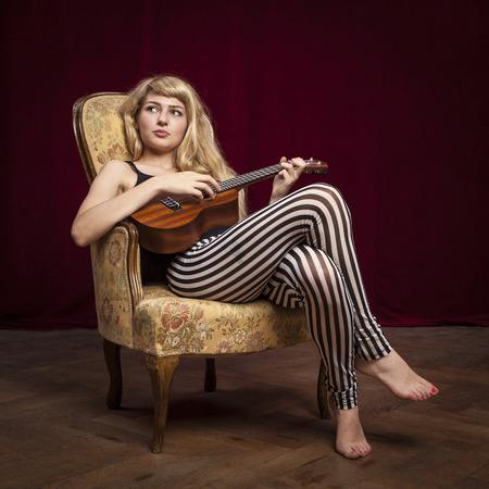 woman guitar: young beautiful blonde woman playing ukulele guitar on a vintage sofa