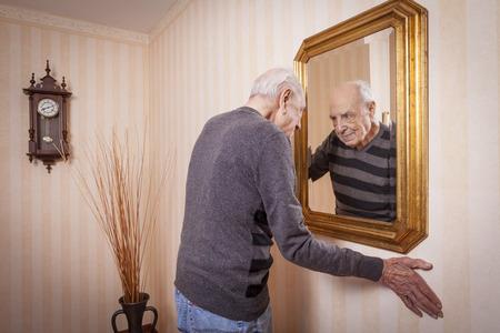 Anziano uomo che guarda se stesso allo specchio Archivio Fotografico - 34826764