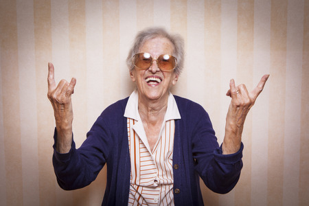 old lady: elder lady making rock on sign