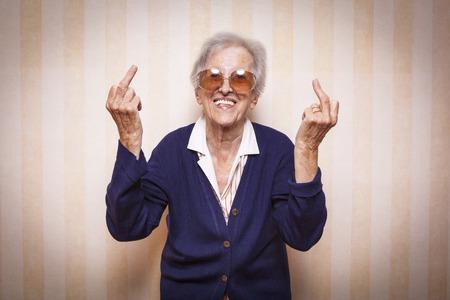 가운데 손가락 기호를 만드는 멋진 노인 아가씨
