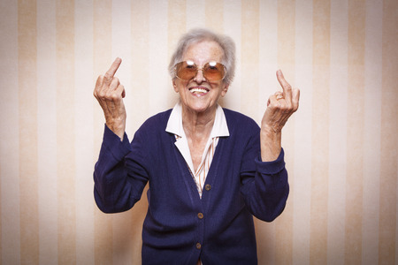 cool elder lady making middle finger sign Stock Photo