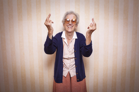 cool elder lady making middle finger sign Stockfoto