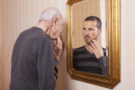 looking at: young man looking at an older himself in the mirror Stock Photo