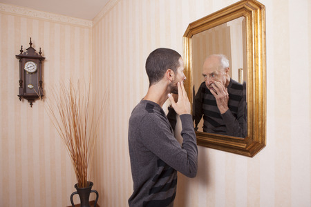 young man looking at an older himself in the mirror Standard-Bild