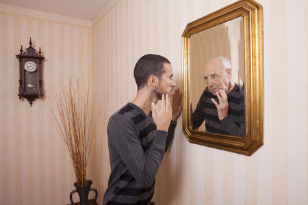 mirror face: young man looking at an older himself in the mirror Stock Photo