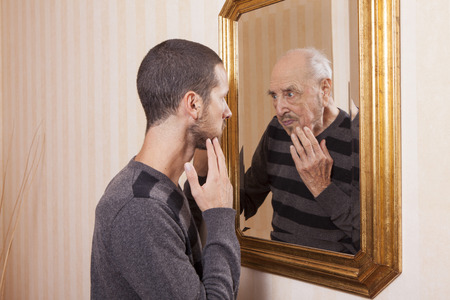 alter ego: young man looking at an older himself in the mirror Stock Photo