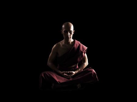 moine: moine bouddhiste en méditation pose sur fond noir Banque d'images