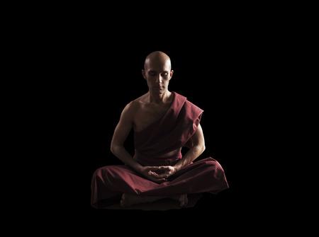 瞑想の僧侶が黒の背景にポーズします。