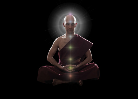 kundalini: buddhist monk in meditation  pose with colorful Chakras over black background