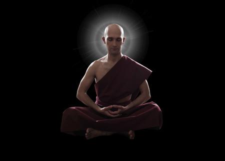 meditation pray religion: buddhist monk in meditation pose over black background