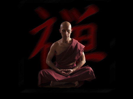 buddhist monk in meditation pose  with zen symbol on the background