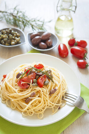 italian spaghetti pasta with cherry tomatoes, olives, capers and rosmary, mediterrean food, vegan recipe