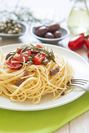 mediterrean: italian spaghetti pasta with cherry tomatoes, olives, capers and rosmary, mediterrean food, vegan recipe