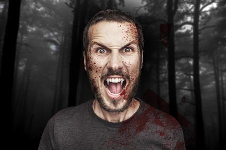 暗い森の背景に美しい怒って男性吸血鬼の potrait