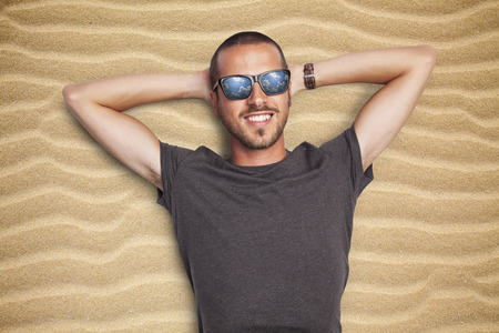 young man enjoying sun on a sandy beach looking at the sky, reflection in the sunglasses Stock Photo