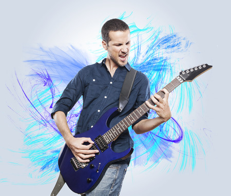 playing music: handsome young man playing electric guitar Stock Photo