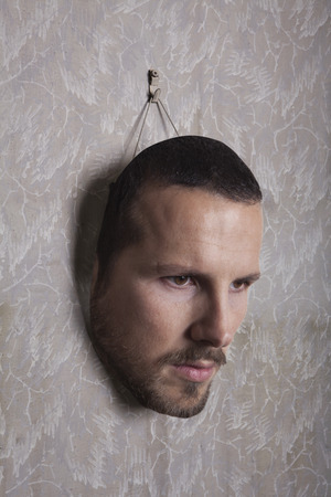 face mask: male human face mask hang on the wall Stock Photo