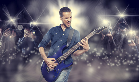 handsome young man playing electric guitar in front of photographers paparazzi Stockfoto