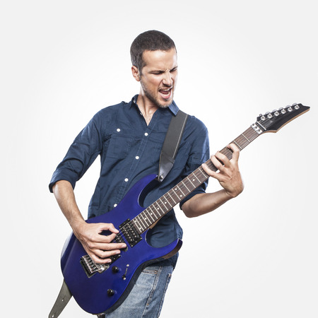 jugando: apuesto joven que toca la guitarra eléctrica