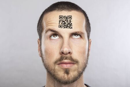 forehead: young man with a qr code on his forehead Stock Photo