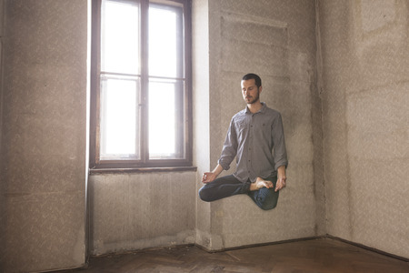 young man levitating in yoga position, meditation Stock Photo