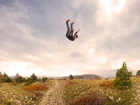 hombre cayendo: hombre cayendo del cielo en paisaje otoñal Foto de archivo