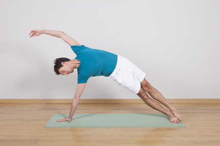 pilates man: man practicing pilates indoor, return to life sequence, 34 exercise