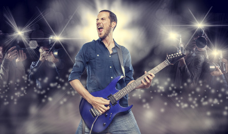 flashes: handsome young man playing electric guitar in front of photographers paparazzi Stock Photo