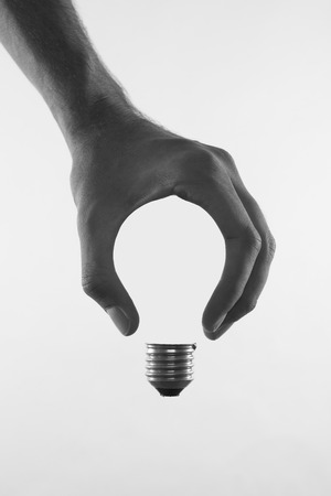 abstract conceptual image of a males hand holding a light bulb shape Imagens