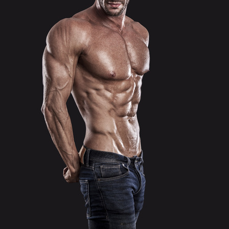 handsome young man: muscle man torso on black background, bodybuilding athlete portrait