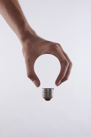 hands of light: abstract conceptual image of a males hand holding a light bulb shape Stock Photo