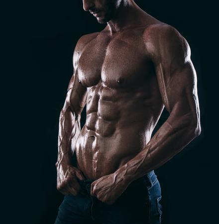 modelos hombres: hombre musculoso torso sobre fondo negro, retrato culturismo atleta