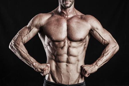 muscle man torso on black background, bodybuilding athlete portrait