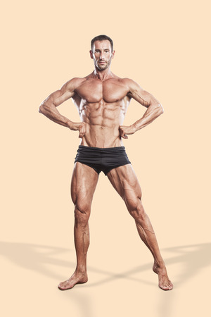 man exercise: muscle man, bodybuilding athlete full body portrait