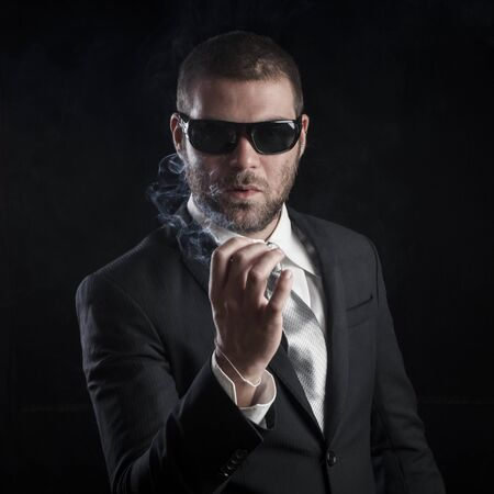 cool guy: portrait of a tough cool man with sunglasses on balck background Stock Photo
