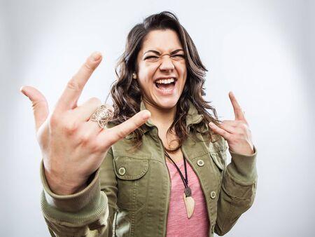 cuernos: Mujer joven que hace gesto de rock cuerno de la mano