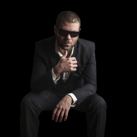 gangster background: portrait of a tough cool man with sunglasses on balck background Stock Photo
