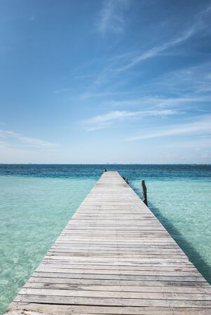 isla: wooden dock into blue tropical sea in Isla Mujeres, Mexico Yucatan